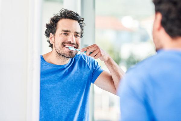 Ein Mann putzt sich vor dem Spiegel die Zähne