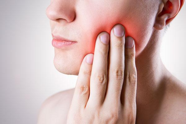 Hand wegen Zahnschmerzen an der Wange