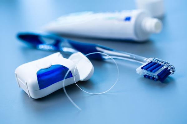 zahnseide, Zahnbürste und Zahnpasta-Tube
